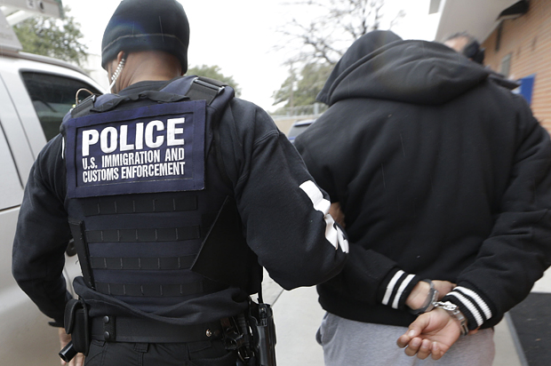 In this photo made Thursday, March 6, 2015, a U.S. Immigration and Customs Enforcement agent escorts a handcuffed undocumented immigrant convicted of a felony that was taken into custody during an early morning operation in Dallas. The Department of Homeland Security has been conducting a nationwide roundup of undocumented immigrants convicted of felonies in order to deport them to their country of origin. (AP Photo/LM Otero)